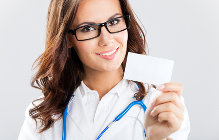 Portrait of happy smiling young female doctor showing blank business card or invitation, over grey background Stock Photo