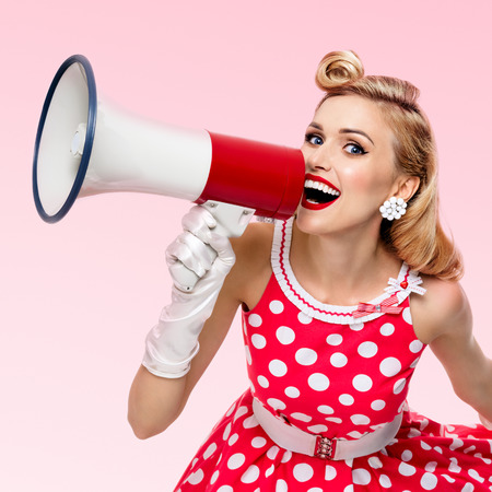 Portrait of woman holding megaphone, dressed in pin-up style red dress in polka dot and white gloves, over pink background. Caucasian blond model posing in retro fashion vintage studio shoot.
