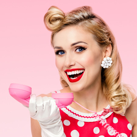 Funny portrait of beautiful happy woman with phone, dressed in pin-up style red dress in polka dot and white gloves, over pink background. Caucasian blond model posing in retro studio shoot. 版權商用圖片