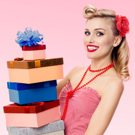 Portrait of beautiful young happy smiling woman in pin-up style clothing, holding gift boxes, over pink background. Caucasian blond model posing in retro fashion and vintage concept shoot.
