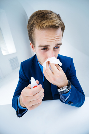 Portrait of ill businessman blowing his nose in handkerchief. Success in business, job and education concept shot.