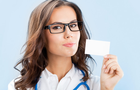 Portrait of happy smiling young female doctor showing blank business card or invitation, over blue background