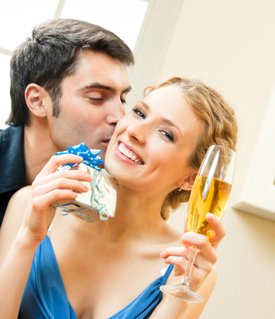 Cheerful amorous couple with gifts, indoors Stock Photo