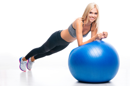 Young cheerful smiling blond woman exercising with fitball, at home or fitness studio, isolated over white background