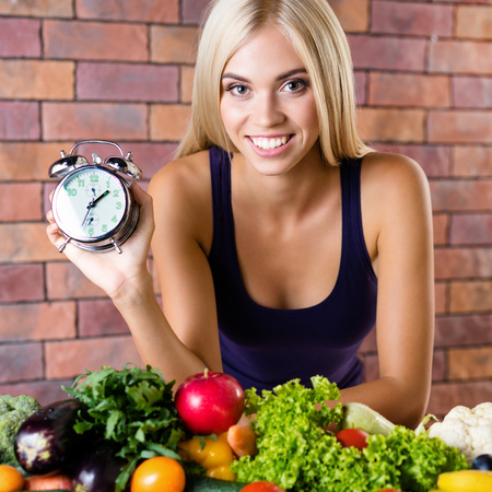 Portrait of happy smiling young beautiful blond woman in fitnesswear, with healthy vegetarian food, at home. Healthy nutrition and time for dieting and fitness concept.