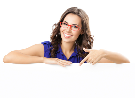 Happy smiling beautiful young woman in blue smart casual clothing and glasses, showing blank signboard or copyspace for slogan or text, isolated against white background Standard-Bild