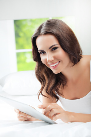 Cheerful young woman using tablet pc, at home