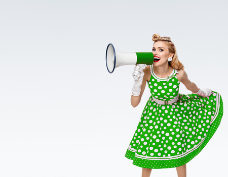 Portrait of woman holding megaphone, dressed in pin-up style green dress in polka dot and white gloves, on grey background, with blank copyspace area for text or slogan. Caucasian blond model posing in retro fashion vintage studio shoot.