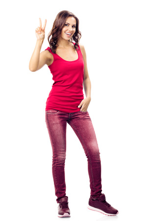 Full body portrait of happy smiling beautiful young woman in casual smart red clothing, showing two fingers or victory gesture, isolated over white background