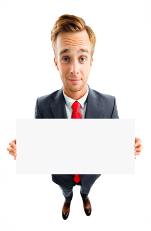 Full body portrait of funny young businessman in confident suit and red tie, showing blank signboard with copyspace area for advertising text or slogan, top angle view shot, isolated over white background. Business concept. Banque d'images