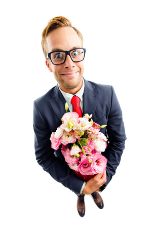 Full body portrait of funny young businessman in glasses, confident suit and red tie, holding bouquet of flowers, top angle view shot, isolated over white background. Business concept. Banque d'images