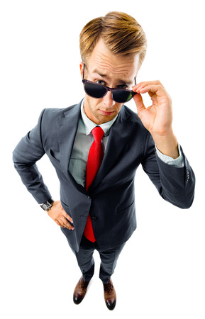 Are you seriously?! Full body portrait of funny skeptic young businessman in black confident suit and red tie, looking through sunglasses, top angle view shot, isolated against white background. Business concept. Banque d'images