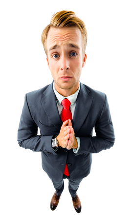 O, please! Full body portrait of funny young businessman in black suit and red tie, press palms together as ask for something or pray gesture, top angle view shot, isolated against white background. Business concept.