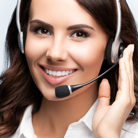 Portrait of happy smiling customer support female phone operator in headset, over grey background. Consulting and assistance service call center concept shot.