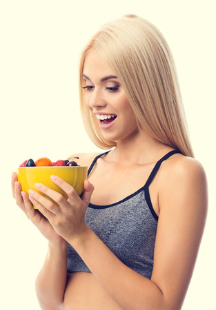 Woman in sportswear with plate of fruits, isolated over yellow background. Young sporty blond model at studio shot. Health, beauty and fitness concept.