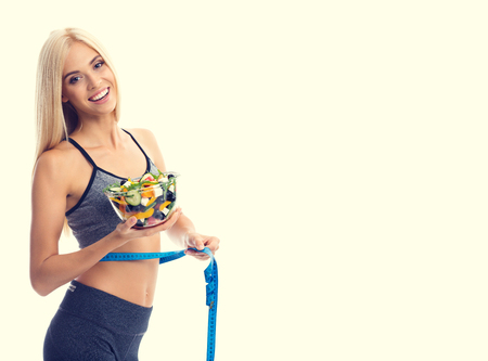 Woman in sportswear with tape measure and salad, with copyspace area for slogan or advertising text message, isolated over yellow background. Young sporty blond model at studio shot. Health, beauty and fitness concept.
