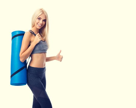 Young cheerful smiling blond woman in sportswear with fitness or yoga mat, showing thumb up, with copyspace area for slogan or advertising text message, isolated over yellow background. Ready for fit exercising concept. Banque d'images