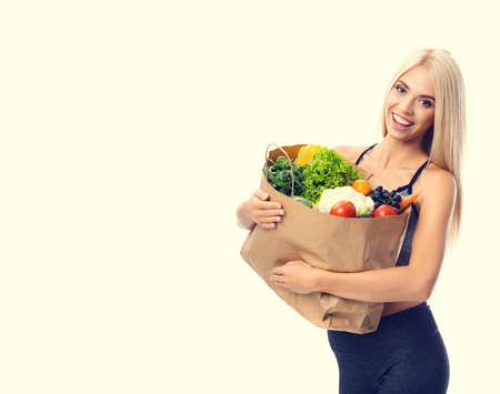Portrait of happy smiling young beautiful woman in fitness wear, holding grocery shopping bag with healthy vegetarian food, with copyspace area for slogan or advertising text message, isolated over yellow background