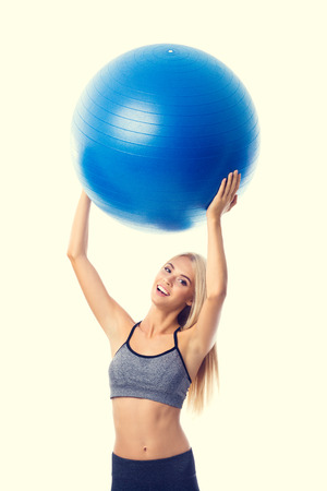 Young cheerful smiling blond woman in sportswear with fitball, isolated over yellow background. Fitness, exercising and fit gym concept.