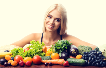 Portrait of happy smiling young beautiful blond woman in fitness wear with healthy vegetarian food, isolated over yellow background Banque d'images