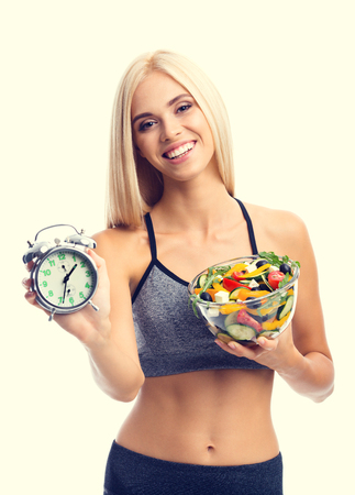 Woman in sportswear with plate of salad and alarm clock, isolated over yellow background. Young sporty blond model at studio shot. Healthy nutrition and time for dieting and fitness concept.