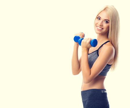 Young happy smiling blond woman in sportswear, doing fitness exercise with dumbbells, with copyspace area for slogan or advertising text message, isolated against yellow background