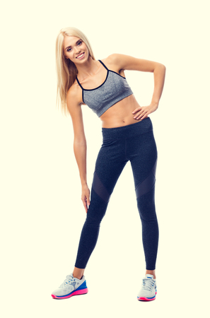 Full body portrait of young happy smiling blond woman, doing fitness exercise, isolated over yellow background