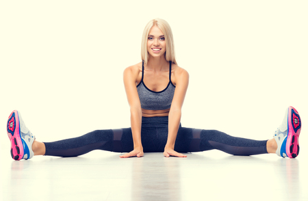 Full body portrait of young happy smiling blond woman, doing exercise, stretching her legs, isolated over yellow background