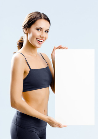 Happy smiling young woman in black fitness wear showing blank signboard with copyspace area for slogan or advertising text message, standing over grey background