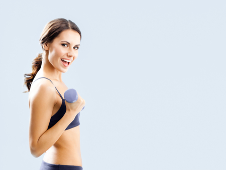 Very happy woman in black fitness wear exercising with dumbbell, with copyspace area for slogan or advertising text message,  standing against blue background Banque d'images