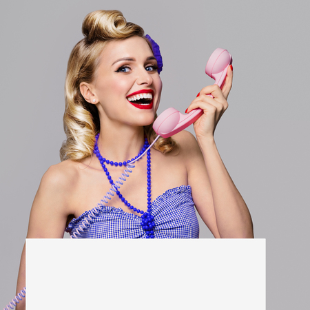 Portrait of beautiful young happy smiling woman with phone and blank signboard, dressed in pin-up style. Caucasian blond model posing in retro fashion and vintage concept studio shoot, on grey background. Banque d'images