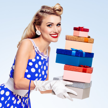 Happy woman in pin-up style blue dress in polka dot and white gloves, holding gift boxes, on blue background. Caucasian blond model posing in retro fashion and vintage shoot. Banque d'images