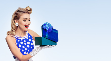 Portrait of beautiful young happy woman dressed in pin-up style dress in polka dot and white gloves, with copyspace area for slogan or advertising text message, on blue background. Caucasian blond model posing in retro fashion shoot.