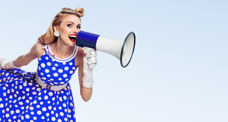 Portrait of woman holding megaphone, dressed in pin-up style dress in polka dot and white gloves, with copyspace area for slogan or advertising text message, on blue background. Caucasian blond model posing in retro fashion vintage shoot.