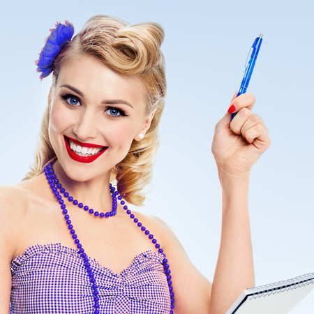 Portrait of beautiful young happy smiling woman with notepad, in pin-up style clothing, on blue background. Caucasian blond model posing in retro fashion and vintage concept studio shoot.