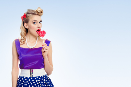 Portrait of woman eating heart shape lollipop dressed in pinup style dress in polka dot, with copyspace area for slogan or advertising text message, on blue background. Caucasian blond model posing in retro fashion and vintage concept shoot.