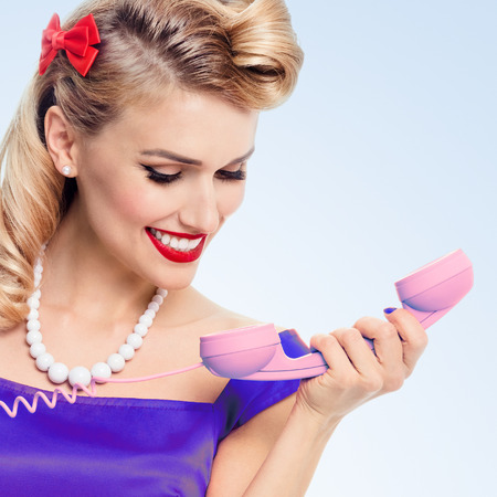 Funny portrait of beautiful woman with phone dressed in pin-up style dress, on blue background. Caucasian blond model posing in retro fashion and vintage concept studio shoot. Banque d'images
