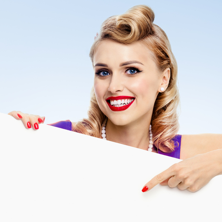 Portrait of smiling young woman in pin-up style, showing blank signboard with copyspace, on blue background. Caucasian blond model posing in retro fashion and vintage concept studio shoot.