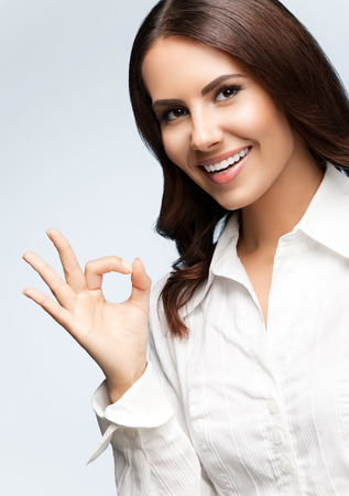 Portrait of happy smiling young cheerful businesswoman, showing okay hand sign gesture, on grey. Success in business concept studio shot.  Banque d'images