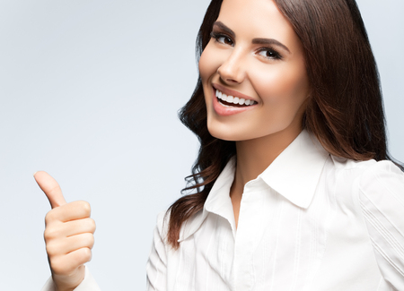 Portrait of happy smiling young cheerful businesswoman, showing thumb up hand sign gesture, on grey background. Success in business concept studio shot.  Banque d'images