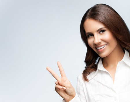 Portrait of happy smiling young cheerful businesswoman, showing two fingers or victory gesture, on grey background, with blank copyspace area for slogan or text. Success in business concept studio shot.