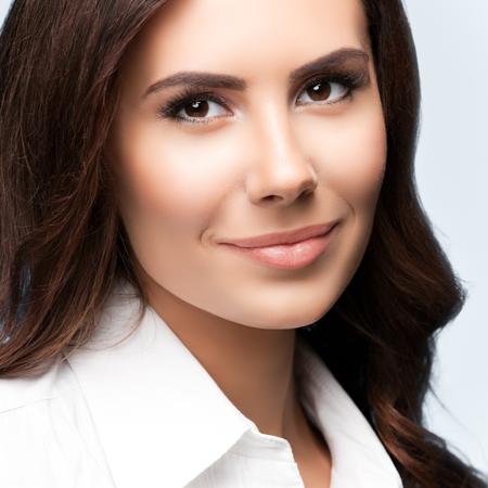 Portrait of happy smiling young cheerful brunette businesswoman, over grey background. Success in business concept studio shot.