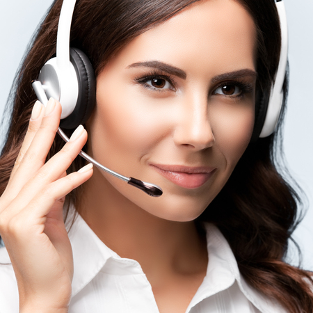 Portrait of customer support female phone worker, against grey background. Consulting and assistance service call center.