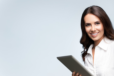 Happy smiling beautiful young brunette businesswoman using no-name tablet pc, over grey background, with blank copyspace area for slogan or text. Success in business concept studio shot.
