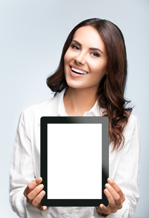 Happy smiling brunette businesswoman showing blank no-name tablet pc monitor, over grey background, with copyspace area for slogan or text message. Success in business concept studio shot.