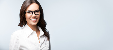 Happy smiling brunette businesswoman in glasses, over grey background, with blank copyspace area for slogan or text. Success in business concept studio shot.
