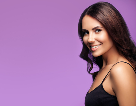 Portrait of beautiful smiling young woman in black top clothing, on violet background, with blank copyspace area for slogan or text