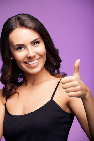 Portrait of beautiful cheerful smiling young woman showing thumb up hand sign gesture, over violet background