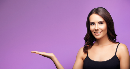 woman in black casual clothing, showing something or blank copyspace area for slogan or text message, on violet background