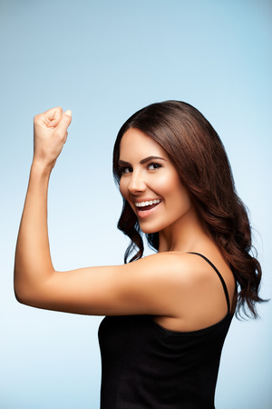 Yes! I done it! Portrait of cheerful smiling young brunette woman happy gesturing, over bright blue background. Success concept studio shot.